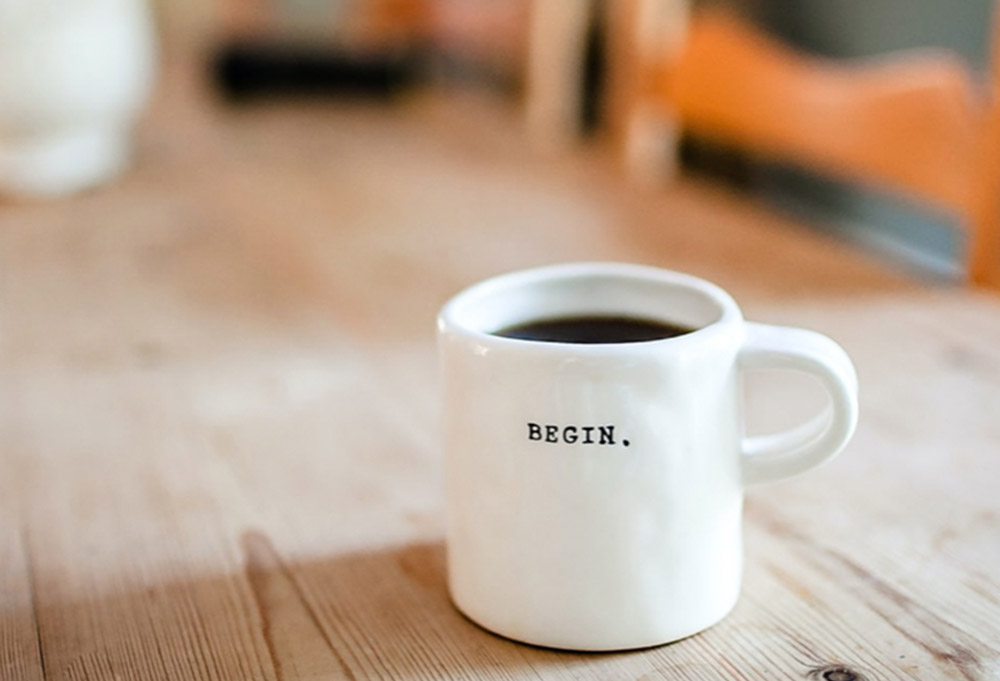 white cup of coffee on table with BEGIN written on it